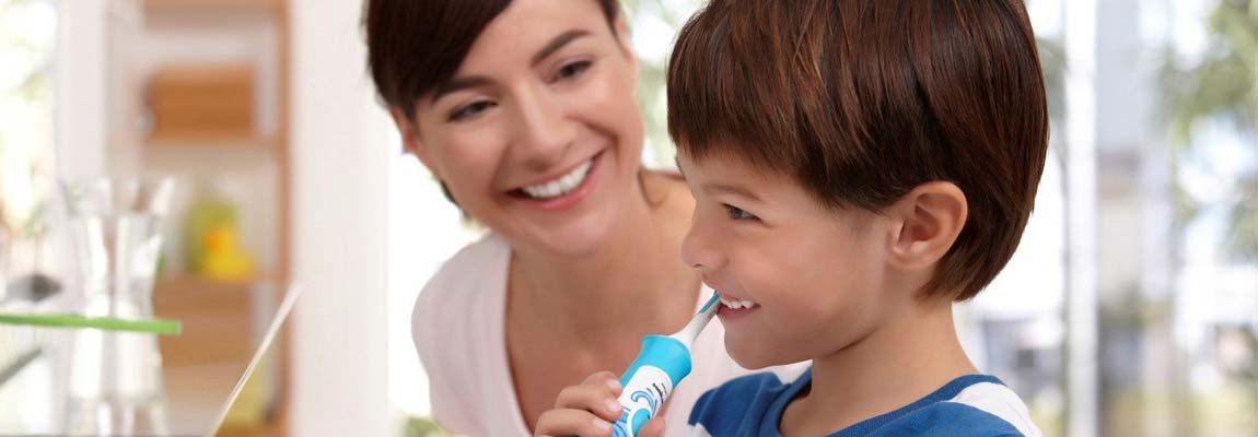 Boy brushing teeth with mother smiling